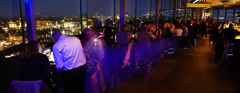 Lassen Sie sich einen Drink in der Bar mit Blick auf die Wolkenkratzer Amsterdams schmecken