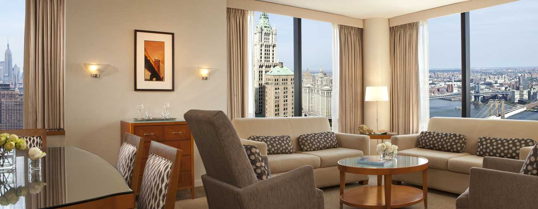 Entspannen Sie auf den gemütlichen Sofas der Suite und genießen Sie den Blick auf die Wolkenkratzer New Yorks