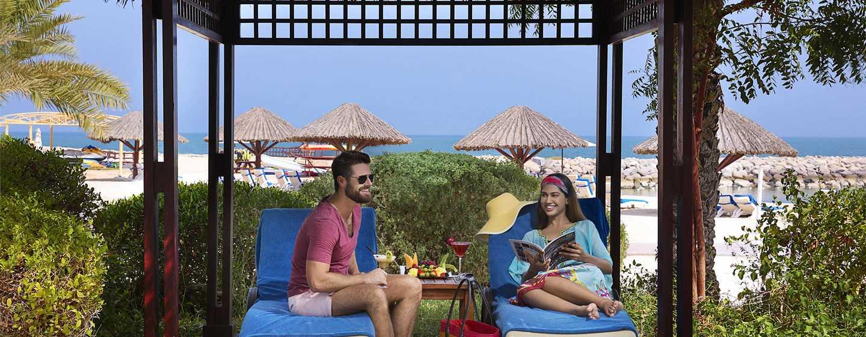 Hilton Ras Al Khaimah Resort & Spa Hotel, VAE– Paar beim Entspannen in einer Pool-Cabana