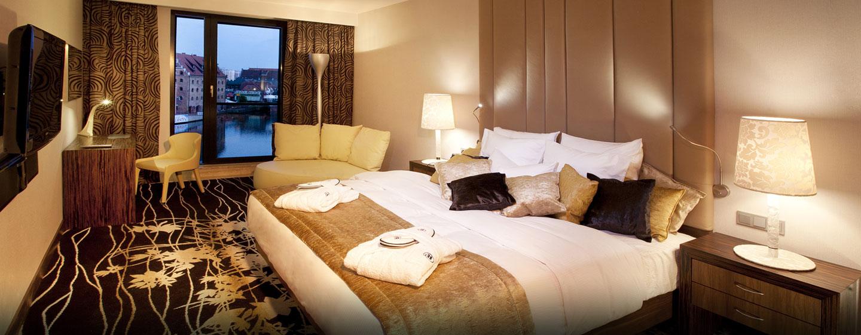Entspannen Sie sich im großen Schlafzimmer der Suite mit Blick auf den Fluss und die Altstadt