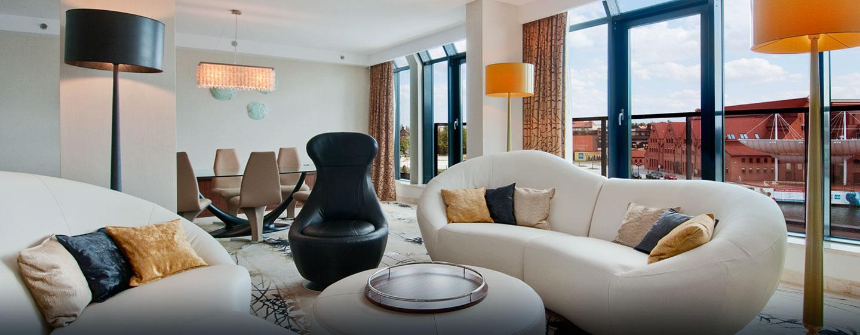 Die designer Möbel und der große Esstisch im Wohnzimmer begeistern die Gäste in der schönen Suite